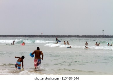 MISSION BAY, CA-USA-11 JULY 2018 Lifeguard controls safety perimeter on Surf Rescue Jet Ski on a day with a strong rip tide while swimmers play in the waves.  There is a rock jetty in the background.