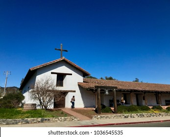 Mission San Francisco Solano in Sonoma California. Daytime color photo horizontal, copy space in blue sky, couple of unrecognizable people next to mission.