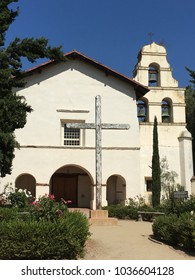 "MISSION SAN JUAN BAUTISTA, CA — JULY 2017: Spanish mission with iconic three-bell wall made famous by the Alfred Hitchcock film ""Vertigo"" with a wooden crucifix in the foreground."