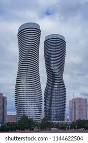 MISSISAUGA, CANADA - JULY 28, 2018:  Absolute World Towers  or Marilyn Monroe Towers  - skyscrapers contominium complex, and the nearby buildings on a cloudy sky background