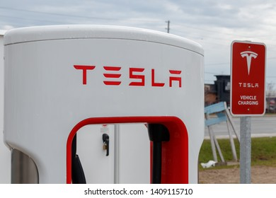 MISSISSAUGA, CANADA - April 23rd, 2019: Top of Tesla Supercharger Stall beside Tesla Vehicle Charging sign.