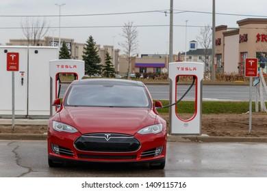 MISSISSAUGA, CANADA - April 23rd, 2019: Front of Red Tesla Model S supercharging in Mississauga at Tesla Supercharger Station.