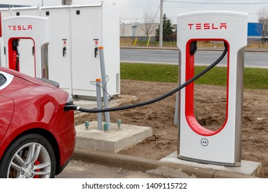 MISSISSAUGA, CANADA - April 23rd, 2019: Closeup of red Tesla Model S plugged-in, charging at a Tesla Supercharger Stall in Mississauga, Ontario.