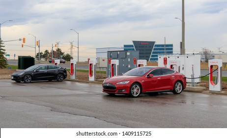 MISSISSAUGA, CANADA - April 23rd, 2019: Red Tesla Model S and Black Tesla Model 3 plugged-in, charging at Tesla Supercharger Station in Mississauga, Ontario.