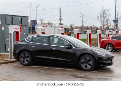 MISSISSAUGA, CANADA - April 23rd, 2019: Black Tesla Model 3 plugged-in, charging at Tesla Supercharger Station in Mississauga, Ontario.