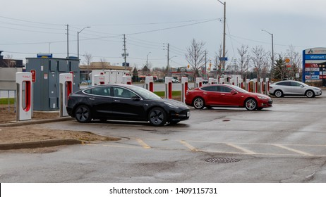 MISSISSAUGA, CANADA - April 23rd, 2019: Tesla Model 3, Model S and Model X plugged-in, charging at a Tesla Supercharger Station in Mississauga, Ontario.