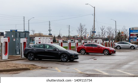 MISSISSAUGA, CANADA - April 23rd, 2019: Black Tesla Model 3, Red Tesla Model S and Silver Tesla Model X plugged-in, charging at a Tesla Supercharger Station in Mississauga, Ontario.