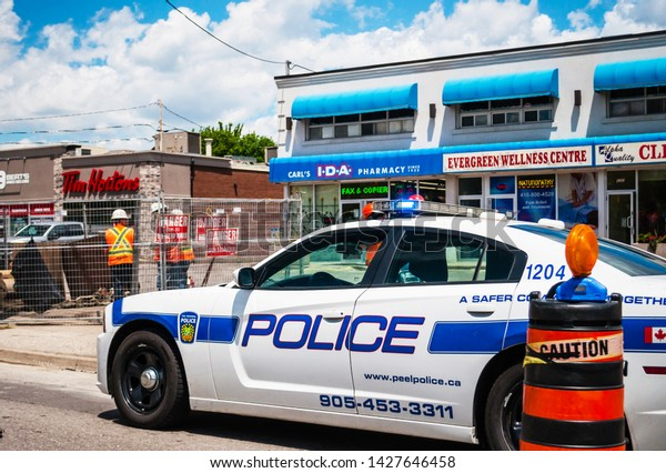 Mississauga, ON, Canada - June 11, 2019: Police vehicle parked on the road near a construction site.