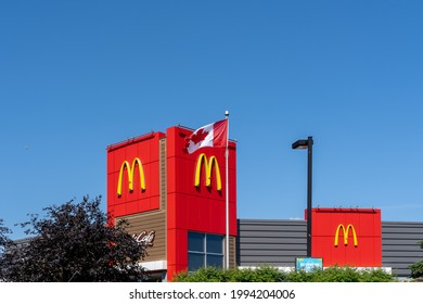 Mississauga, ON, Canada - June 12, 2021: McDonald's logo on the building with a Canadian flag. McDonald's Corporation is an American fast food company.