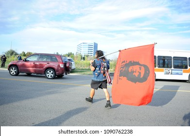 "MISSISSAUGA-AUGUST 25:An activist carrying a flag with the picture of""che guevara to protest the death of Abdirahman Abdi-a Somali-Canadian killed by Ottawa Police on August 25 2016 in Mississauga,"