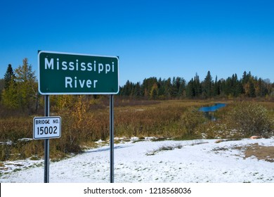 Mississippi River flowing north near its source at Itasca State Park in Minnesota. This sign is at the second highway bridge over the Mississippi River after an early autumn snowfall.