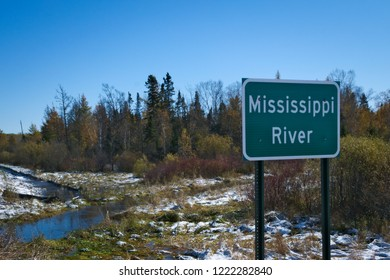 Mississippi River flowing north near its source at Itasca State Park in Minnesota. This sign is at the fifth highway bridge over the Mississippi River after an early autumn snowfall.