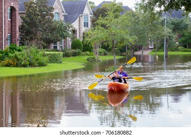 Missouri City, Texas - August 30, 2017: Residents of Sienna Plantation taking canoe rides in flooded street. Heavy rains from hurricane Harvey caused many flooded areas in Houston suburbs