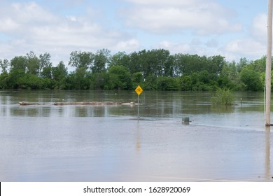 Missouri river overflowing its banks.  Water levels rose high enough to cover a multi user trail, which can only be seen by the bike crossing sign poking out of the flood water.  May 29th 2019.