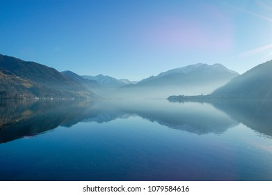 Mist above blue lake in the mountains. Zell am See, Austria.