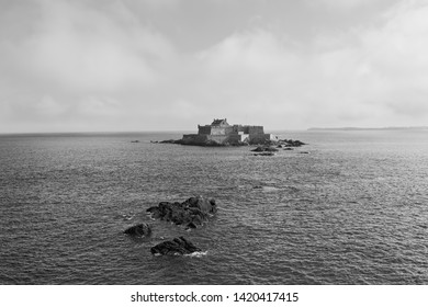 Mist begins to lift around Fort National and its tiny island near St Malo. Black and white image