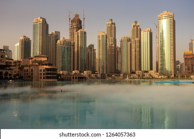 Mist, caused by musical fountain testing, lingering over Burj Khalifa lake, just after sunrise. Skyline comprised of skyscrapers hit by first rays of sun and clear sky in the background. In Dubai, UAE