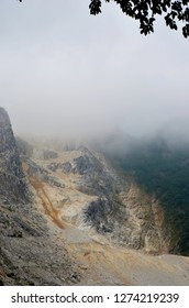 Mist covers a rock path through the mountains. The rocks are made of marble. Forest can be seen in the distance, and the leaves of a tree frame the view.
