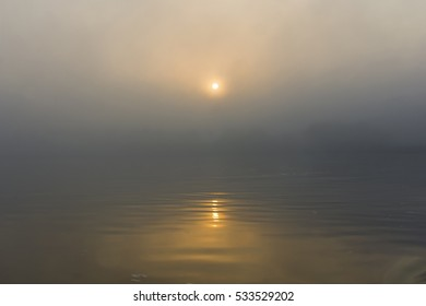 Mist and Fog on a foggy River while the sun rises. Beautiful soft colors are created by the yellow sunlight