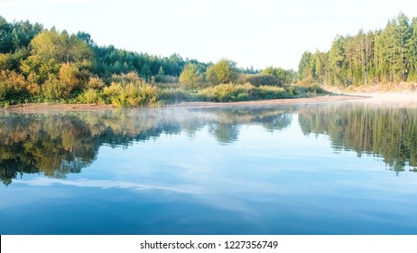 Mist over the river. Autumn forest is reflected in the water on the riverbank.