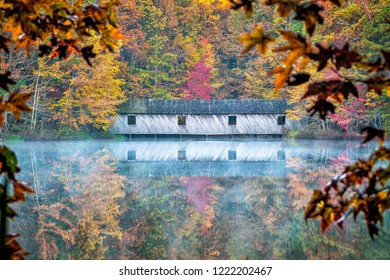 As mist rises from the calm waters, fall colors are reflected around the covered bridge.