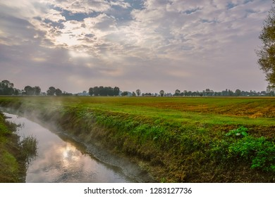 Mist rising from an irrigation ditch in a natural park during autumn