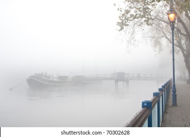 Mist shrouded jetty on river with streetlight
