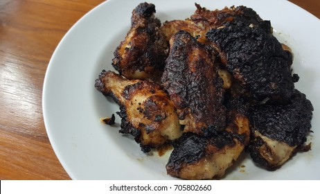 Mistake cooking,  black burning chicken on a white plate picture.
