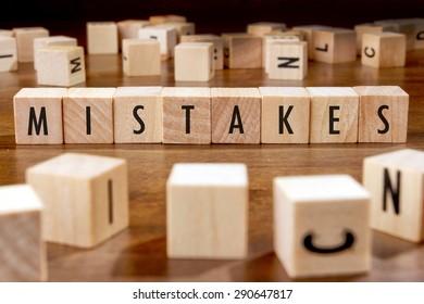 MISTAKES word written on wood block