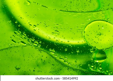 Misted glass, green rain drops dew drops on colorful abstract cool color background condensation on tinted vibrant glass window