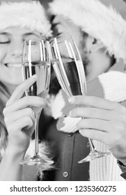 Mister and Missis Claus hold glasses of champagne, close up. Man with beard and woman with smiling faces on background, defocused. Christmas party concept. Santa and sexy girl with drinks cuddle