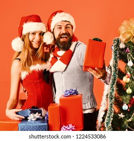Mister and Missis Claus with red and blue presents near fir tree. Couple in love with xmas gift boxes. Christmas presents and love concept. Man with beard and woman with happy faces on red background