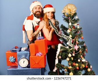 Mister and Missis Claus with red and blue gifts near fir tree. Santa and sexy girl decorate xmas tree. New Year and Christmas time concept. Man with beard and woman with happy faces on blue background