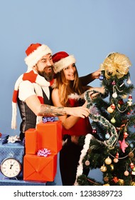 Mister and Missis Claus with red and blue gifts near fir tree. Christmas gifts and love concept. Santa and sexy girl decorate xmas tree together. Man and woman with happy faces on blue background