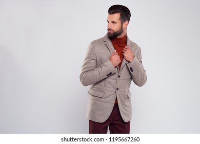 Mister perfection. Handsome young man adjusting his jacket while standing against white background