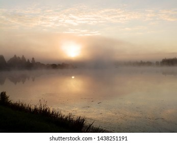 mistic fog in the morning, lake at dawn with clouds reflected in the calm water, Latvia