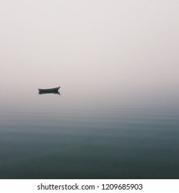 Mistic lonely boat in the middle of the lake, mist fog