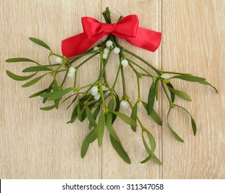 Mistletoe with red ribbon bow over light oak wood background.