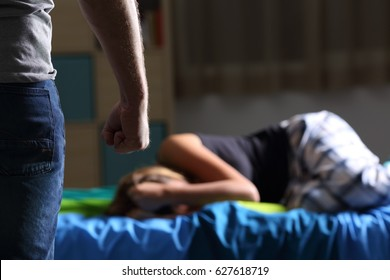 Mistreatment victim lying on the bed of her bedroom and abuser fist in foreground with a dark light in the background