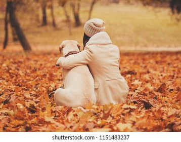 Mistress Hugging with Dog. Autumn Park. Beautiful Outdoors. Walking with Animals. Pets and People. Labrador Retriever. Autumn Background. Dog and Leaves. Pet and Owner Portrait. Attractive Labrador.