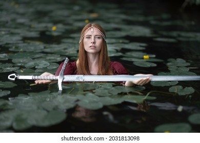 The mistress of the lake among the leaves of water lilies gives a medieval sword