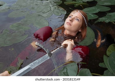 The mistress of the lake among the leaves of water lilies lies on the water with a sword on her chest