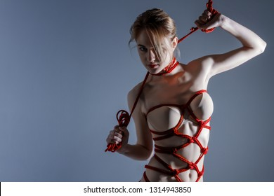 Mistress master dominant woman bound in erotic fashion rope shibari kinbaku Japanese bondage knot with collar around neck holding a whip rope. Bdsm sadomasochism submission slave fetish punish concept