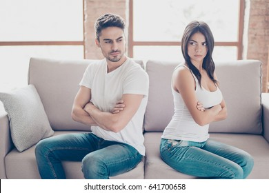 Mistrust and cheat problems. Annoyed couple is ignoring each other, sitting on the couch back to back indoors at home