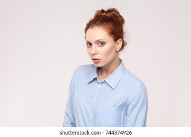Mistrust and puzzled redhead woman, looking at camera. Studio shot