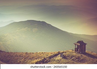 Misty autumn mountain hills landscape. Small chapel with mountains in the background. Filtered image:cross processed vintage effect.