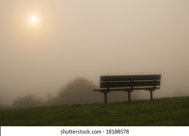 misty bench on a hill under the raising sun in the morning fog, soft focus