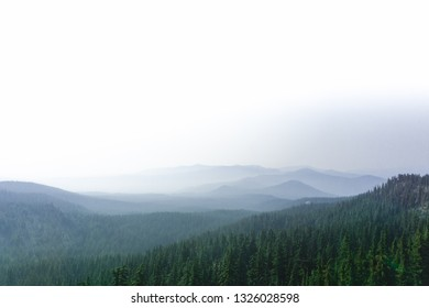 Misty blue and green mountain range with bright white and grey hazy cloud covering in California along the Pacific Crest Trail