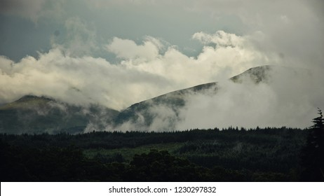 Misty clouds over green hills in the Scottish Highlands