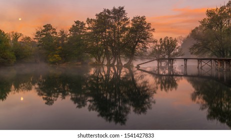Misty and colorful morning sunrise and moonset over a river with a wooden bridge